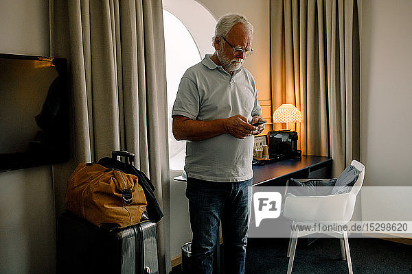 Älterer Mann benutzt Smartphone  während er im Hotelzimmer steht Älterer Mann benutzt Smartphone, während er im Hotelzimmer steht