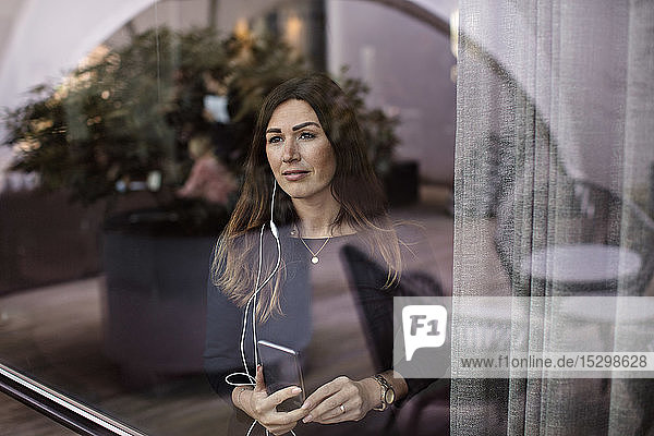 Geschäftsfrau  die Musik hört  während sie im Büro am Fenster steht Geschäftsfrau, die Musik hört, während sie im Büro am Fenster steht