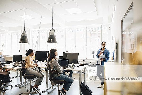 Computerprogrammierer  der Kollegen während einer Besprechung im Kreativbüro den Code erklärt