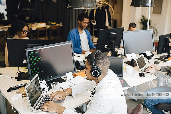 High angle view of businessman with headphones coding over laptop while coworkers working in background