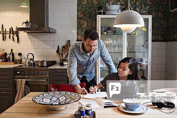 Vater führt Sohn bei den Hausaufgaben zu Hause