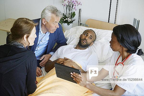 Hochwinkelansicht eines Arztes  der über ein digitales Tablett mit Patient und Familie auf der Krankenhausstation diskutiert Hochwinkelansicht eines Arztes, der über ein digitales Tablett mit Patient und Familie auf der Krankenhausstation diskutiert