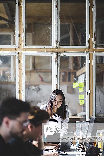 Zuversichtlicher weiblicher IT-Fachmann betrachtet Kollegen bei der Codierung von Laptops am Arbeitsplatz