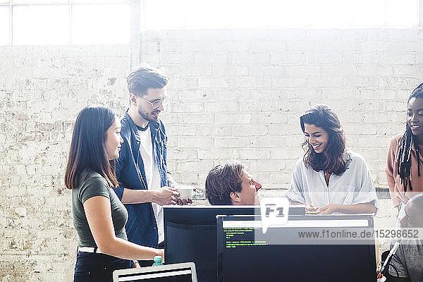 Zuversichtliche professionelle Hacker diskutieren beim gemeinsamen Codieren in IT-Firma