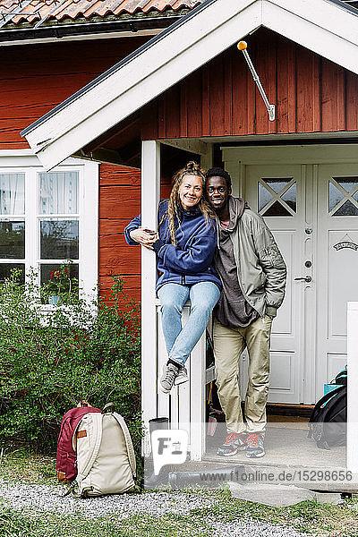 Porträt von lächelnden Freunden mit Rucksäcken am Hütteneingang am Wochenende