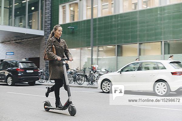 Selbstbewusste Geschäftsfrau fährt Elektroroller in voller Länge auf der Straße in der Stadt