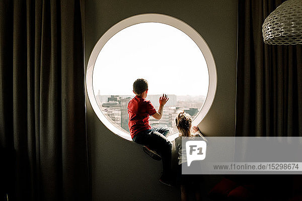 Geschwister am Fenster im Hotelzimmer
