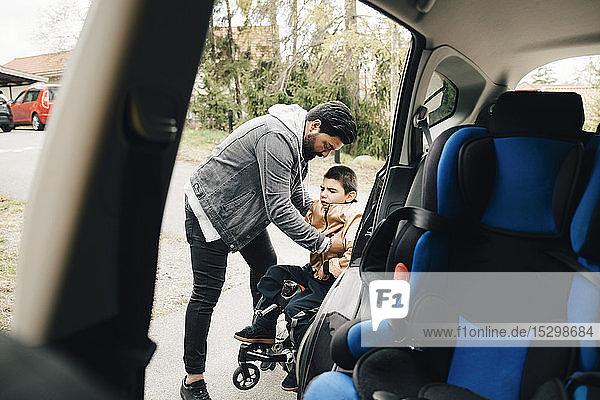 Vater trägt behinderten Sohn aus dem Rollstuhl vom Auto aus gesehen