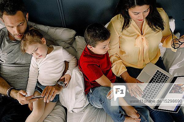 Direkt über der Aufnahme von Eltern  die Technologien einsetzen  während sie mit Kindern im Bett sitzen