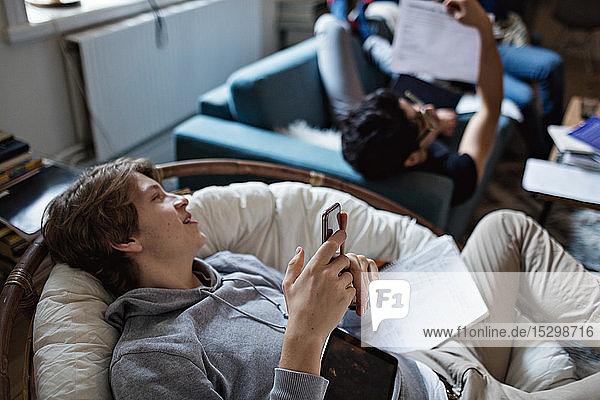 Abgelenkter Teenager nutzt soziale Medien auf dem Handy  während er mit einem Freund zu Hause lernt Abgelenkter Teenager nutzt soziale Medien auf dem Handy, während er mit einem Freund zu Hause lernt