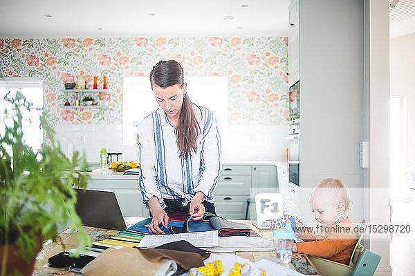 Modedesignerin wählt Stoff aus Stoffmustern aus  während die Tochter in der Küche am Tisch spielt