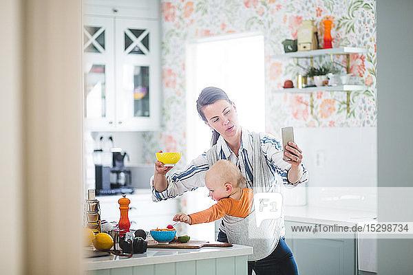 Multi-Tasking-Blogging über Mutter-Essen  während die Tochter in der Küche zu Hause ist Multi-Tasking-Blogging über Mutter-Essen, während die Tochter in der Küche zu Hause ist