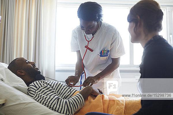 Ärztin untersucht Patientin durch Besucher bei Routinekontrolle auf der Krankenhausstation