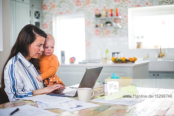 Female entrepreneur carrying loving daughter while using laptop on dining table at home office
