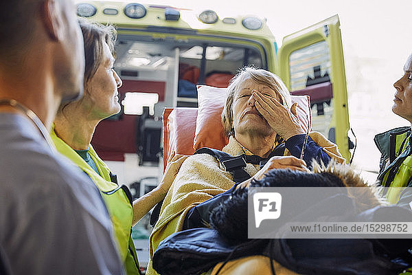 Sanitäter tröstet kranken reifen Patienten auf Krankenhausbahre Sanitäter tröstet kranken reifen Patienten auf Krankenhausbahre