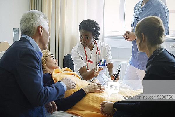 Arzt und Krankenschwester erklären der reifen Patientin und ihren Freunden auf der Krankenhausstation