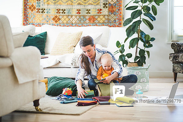 Full length of multi-tasking mother with fabric swatches and daughter working in living room at home