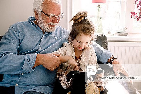 Mädchen benutzt digitales Tablet  während sie mit Großvater zu Hause auf dem Sofa sitzt
