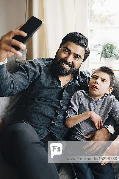 Smiling father taking selfie with autistic son while sitting on sofa in living room