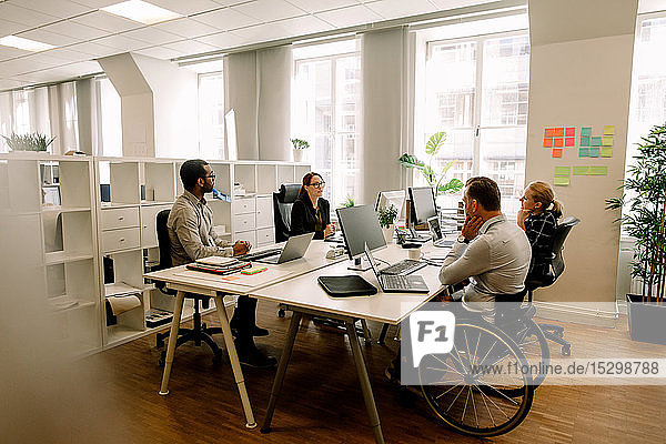 Business colleagues with disabled sales manager working at desk in office
