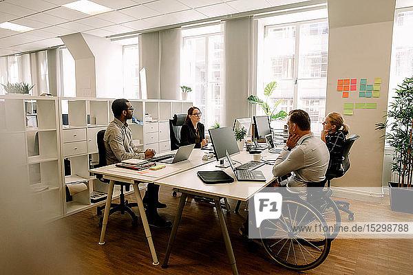 Geschäftskollegen mit behinderten Verkaufsmanagern  die am Schreibtisch im Büro arbeiten