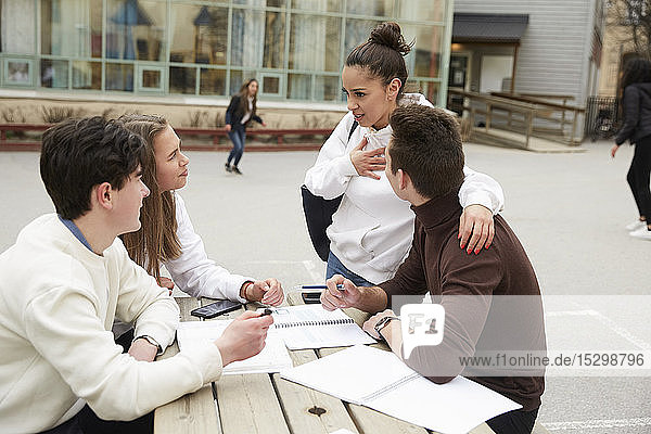 Teenage girl talking with male and female friends studying at table in schoolyard