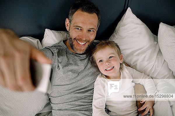 Schrägaufnahme eines glücklichen Vaters  der sich mit einer lächelnden Tochter auf dem Bett im Hotel eingenommen hat