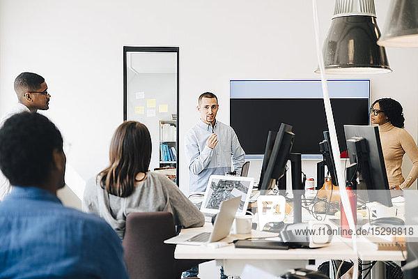 Computerhacker schauen auf Programmierer  der während einer Sitzung im Kreativbüro eine Präsentation hält