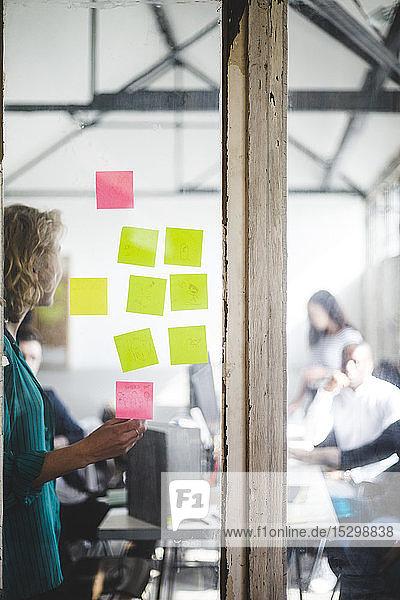 Geschäftsfrau hält Präsentation vor IT-Fachleuten durch Glaswand im Kreativbüro