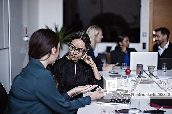 Geschäftsleute  die am Konferenztisch im Sitzungssaal arbeiten