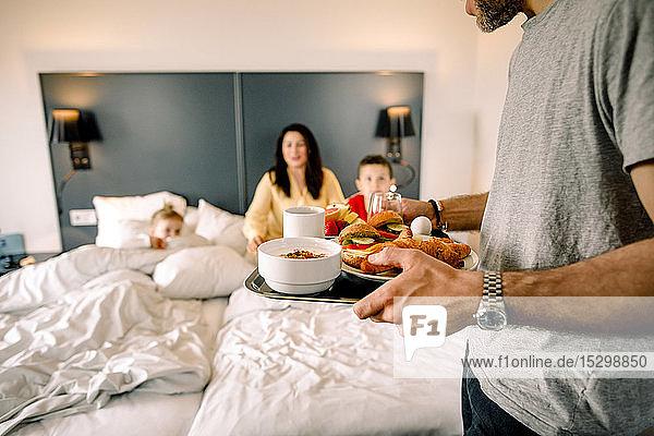 Vater frühstückt mit der Familie  die im Hintergrund auf dem Bett sitzt