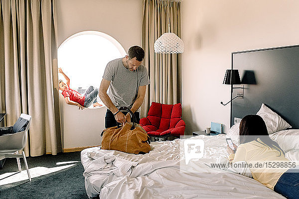 Man packing bag while woman using phone on bed in hotel