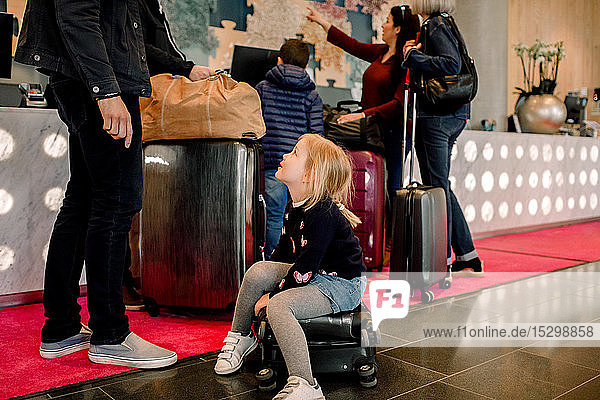 Mädchen sitzt auf einem Koffer und sieht den Vater an  während die Familie im Hintergrund steht
