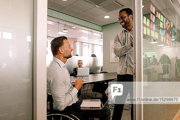 Lächelnder Geschäftsmann sieht behinderten Kollegen im Sitzungssaal an  der im Rollstuhl sitzt