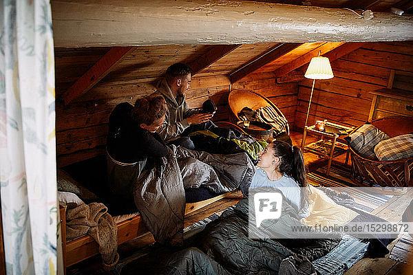 Hochwinkelansicht von Freundinnen und Freunden  die sich unterhalten  während sie zur Schlafenszeit in einer Hütte ruhen Hochwinkelansicht von Freundinnen und Freunden, die sich unterhalten, während sie zur Schlafenszeit in einer Hütte ruhen