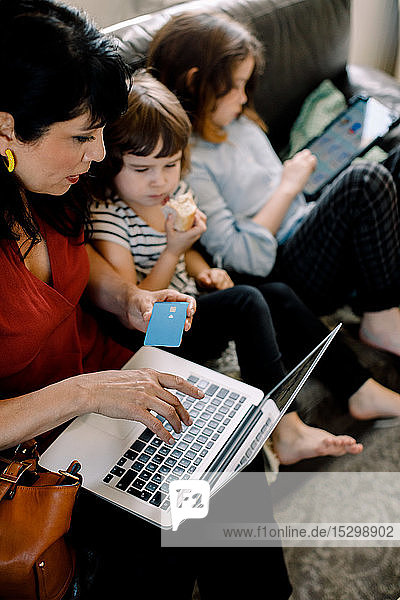 High angle view of woman doing online shopping through laptop while sitting with daughters at home