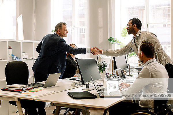 Businessmen shaking hands during sales meeting in office