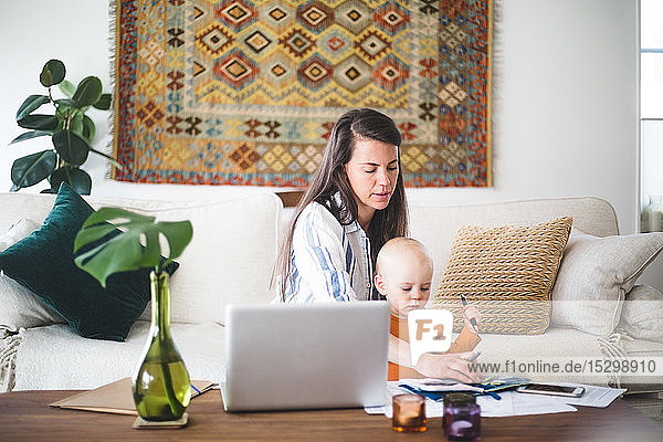 Busy female parent running business while taking daughter's care at home