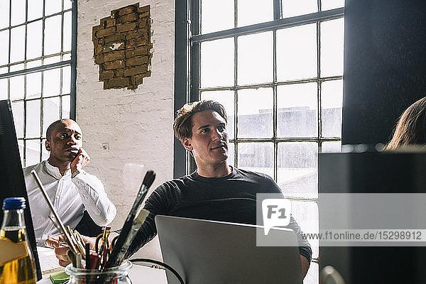 Selbstbewusste männliche IT-Fachleute schauen weg  während sie während einer Sitzung im Sitzungssaal sitzen Selbstbewusste männliche IT-Fachleute schauen weg, während sie während einer Sitzung im Sitzungssaal sitzen