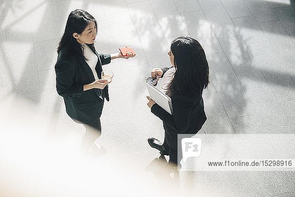 Schrägaufnahme von Kolleginnen  die während eines Gesprächs im Büro Kaffee trinken