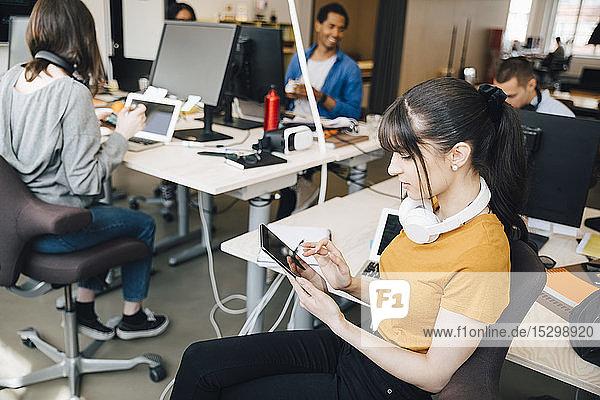 Weibliche IT-Computerhackerin nutzt digitales Tablet  während ihre Kollegen im Kreativbüro arbeiten