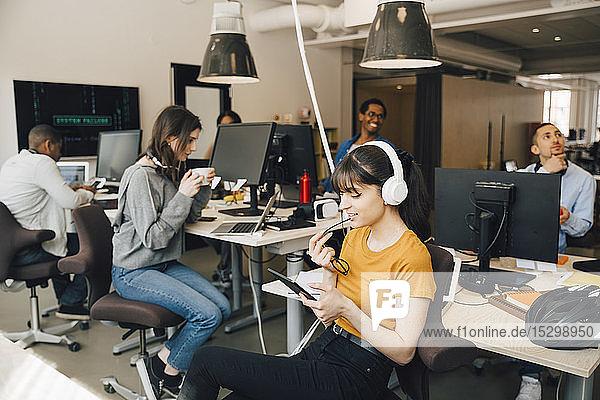 IT-Fachfrau verwendet digitales Tablet  während ihre Kolleginnen im Hintergrund im Kreativbüro arbeiten
