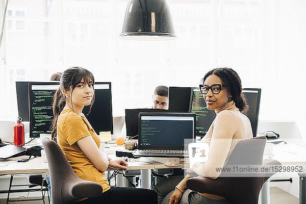 Portrait weiblicher Computer-Hacker am Schreibtisch im Kreativbüro