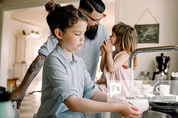 Mädchen wäscht Becher am Waschbecken  während der Vater in der Küche mit der Tochter spricht Mädchen wäscht Becher am Waschbecken, während der Vater in der Küche mit der Tochter spricht