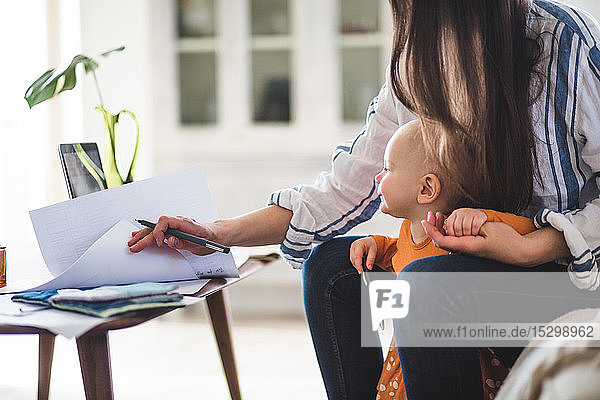 Midsection of working mother examining documents with baby girl at home office