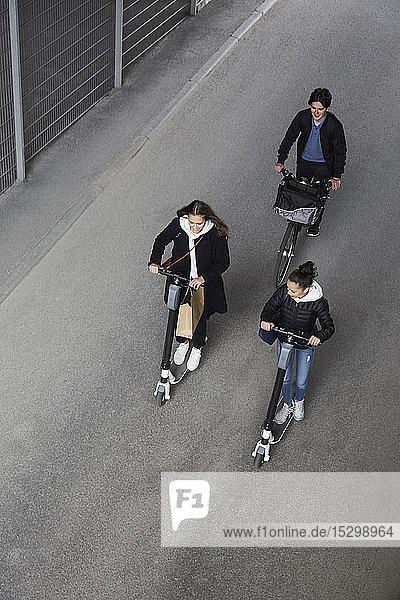 Hochwinkelaufnahme von Freundinnen und Freunden  die auf Elektrorollern und Fahrrädern auf der Straße in der Stadt fahren Hochwinkelaufnahme von Freundinnen und Freunden, die auf Elektrorollern und Fahrrädern auf der Straße in der Stadt fahren