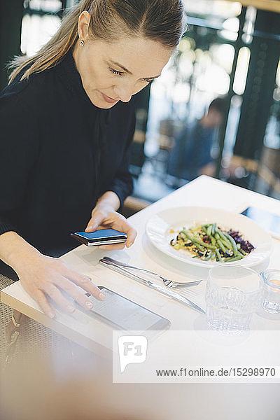 Selbstbewusste Unternehmerin benutzt Mobiltelefon  während sie mit Kreditkarte in der Cafeteria im Büro sitzt