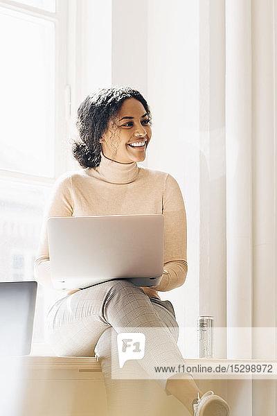 Lächelnde Frau schaut weg  während sie den Laptop am Schreibtisch im Büro benutzt