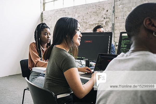 Selbstbewusste weibliche und männliche IT-Fachleute sitzen während einer Sitzung am kreativen Arbeitsplatz im Sitzungssaal