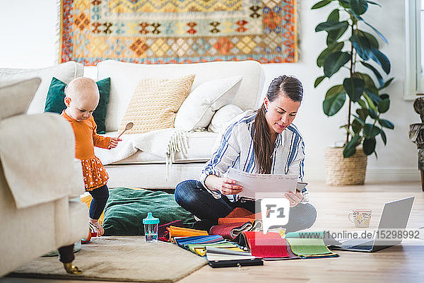 Fashion designer examining papers while daughter playing in living room